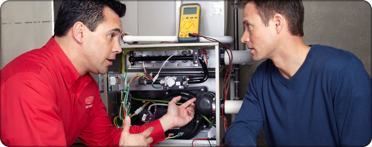 Furnace repair technician discussing the homeowner's furnace questions